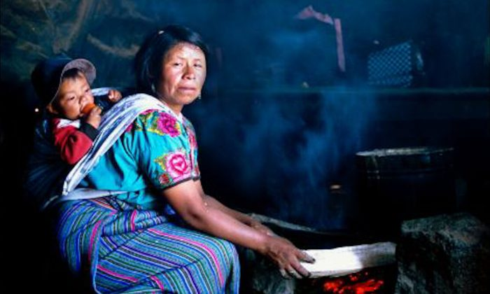 A woman in Guatemala cooks over an open fire with her child swaddled to her back. (Courtesy Nigel Bruce)