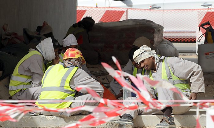 Asian labourers take a break during work on road network construction site in eastern Riyadh on April 7, 2013. Saudi Arabia has given illegal foreign workers a three-month grace period to legalize their status, after panic over reported mass deportations, an official statement said. (FAYEZ NURELDINE/AFP/Getty Images)
