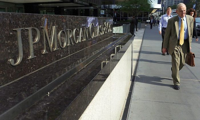 People pass a sign for JPMorgan Chase & Co. at its headquarters in New York City in this file photo. Banking sector experts suggest that JPMorgan and other highly regarded financial institutions consider paying fines as a cost of doing business. (Spencer Platt/Getty Images)