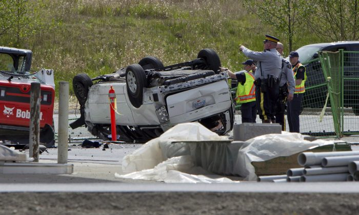 RCMP officers investigate the aftermath of a fatal car crash that killed five people in Surrey, B.C., last month. Family members of officers afflicted with PTSD want the force to do more to help officers cope with the horrors faced while on the job. (THE CANADIAN PRESS/Eric Dreger)