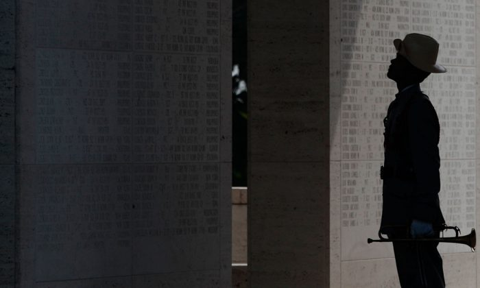 4. A Filipino trooper looks at walls inscribed with names of fallen U.S. soliders during Memorial Day rites at the American Cemetery in suburban Taguig, south of Manila, Philippines on Sunday, May 26, 2013. The cemetery contains the largest number of American soldiers who lost their lives in World War II. (AP Photo/Aaron Favila)