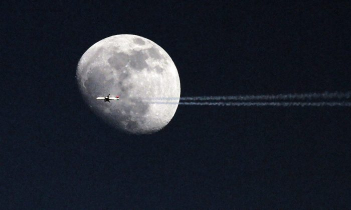 An airplane passes in front of the moon over Philadelphia. A telescope that is set to launch to the moon in 2015 will allow the public to go on the Internet and view the Earth from the lunar surface. (AP Photo/ Joseph Kaczmarek)