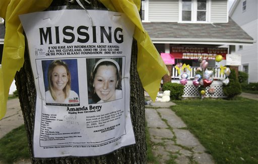 A missing poster still rests on a tree outside the home of Amanda Berry Wednesday, May 8, 2013, in Cleveland. Berry, 27, Michelle Knight, 32, and Gina DeJesus, had apparently been held captive in a nearby house since their teens or early 20s, police said. (AP Photo/Tony Dejak)