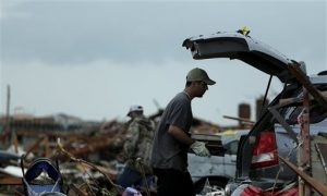 Justin Stehan salvages photographs from his tornado-ravaged home Tuesday, May 21, 2013, in Moore, Okla. A huge tornado roared through the Oklahoma City suburb Monday, flattening entire neighborhoods and destroying an elementary school with a direct blow as children and teachers huddled against winds. The search for survivors and bodies is almost complete, says the city's fire chief. (AP Photo/Charlie Riedel)