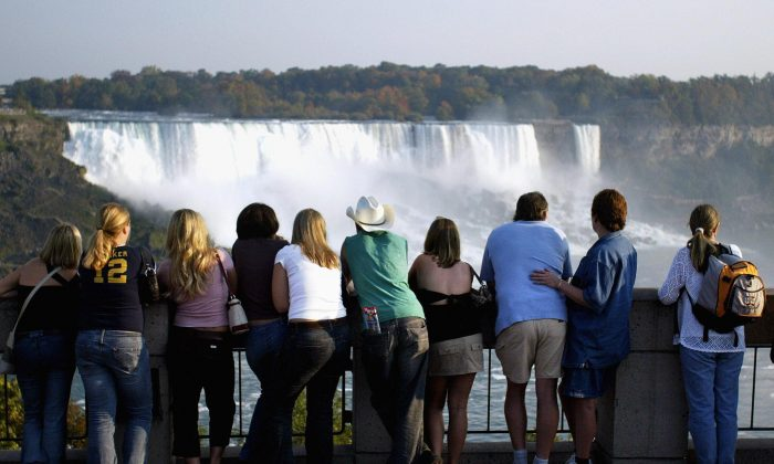Tourists look out at Niagara Falls from the Canadian side of the Canada/U.S. border. Canada is halting efforts to attract U.S. tourists after years of largely failing to draw Americans from other leisure destinations. (Don Emmert/AFP/Getty Images)