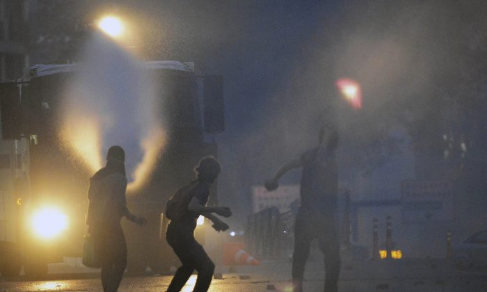 Riot police use tear gas and pressurized water to quash a demonstration by hundreds of people trying to prevent the demolition of trees at an Istanbul park, Turkey, May 31, 2013. (AP Photo)