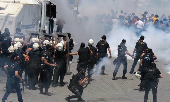 Riot police clash with demonstrators after they used tear gas and pressurized water in a dawn raid Friday to rout a peaceful demonstration by hundreds of people staging a sit-in to prevent the uprooting of trees at an Istanbul park, May 31. (AP Photo)