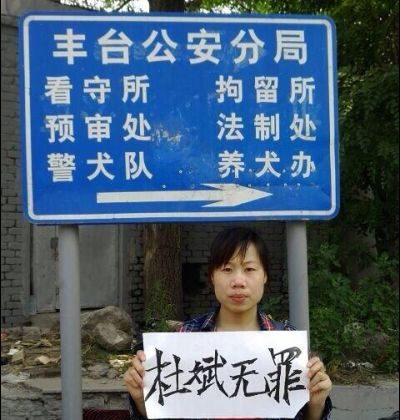 "Du Jirong, sister of human rights activist Du Bin, holds up a sign saying ""Du Bin is innocent."" outside the Fengtai District Public Security Bureau. (China Human Rights Defenders)"