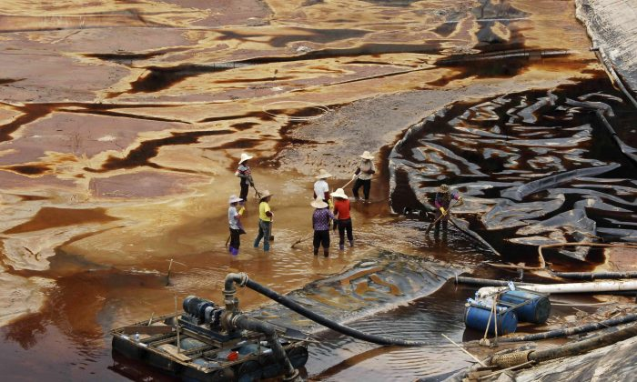 "Workers drain away polluted water near the Zijin copper mine in Shanghang on July 13, 2010, after pollution from the mine contaminated the Ting River, a major waterway in southeast China's Fujian Province. Such pollution has been an integral part of the development of China's economy—the ""China model"" that the Chinese regime is now exporting around the world. (STR/AFP/Getty Images)"