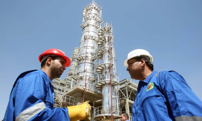 Iraqi workers stand outside the second refinery for crude oil in the Al-Dora refinery complex during its official opening ceremony in Baghdad on Sept. 16, 2010. A boom in oil investment and exports is fueling economic growth attracting foreign companies and capital. (Ahmad Al-Rubaye/AFP/Getty Images)