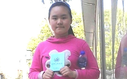 Zhang Lin, a democracy activist in China, and his ten-year-old daughter, Anni, have escaped from house arrest in Anhui Province. In this photo, Anni is holding a copy of the Universal Declaration of Human Rights to express her hope that she will be allowed to return to school. (Screenshot from Internet)