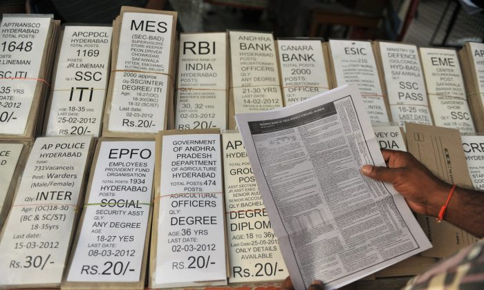 Indian youth checks job application forms at a shop in Hyderabad. India might lead the world in turnover rates at 26.9 percent in the coming year according to a study.  (Noah Seelam/AFP/Getty Images)