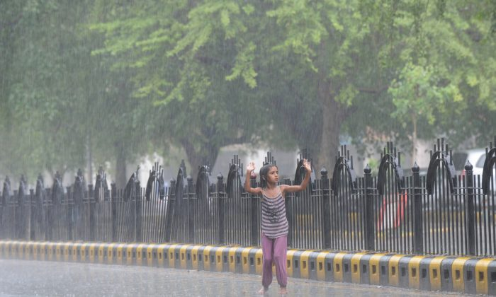 An Indian street child dances in the middle of a road as monsoon rains fall in New Delhi on June 16, 2013. (Sajjad Hussain/AFP/Getty Images)