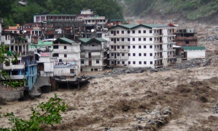Fast moving water from the  Alaknanda river destroys building during a heavy monsoon rain in Govindghat town in the Indian state of Uttrakhand on June 17, 2013. Heavy rains lashed parts of north India Monday, resulting in the deaths of hundreds , as the annual monsoon covered the country nearly two weeks ahead of schedule, officials said. (STRDEL/AFP/Getty Images)