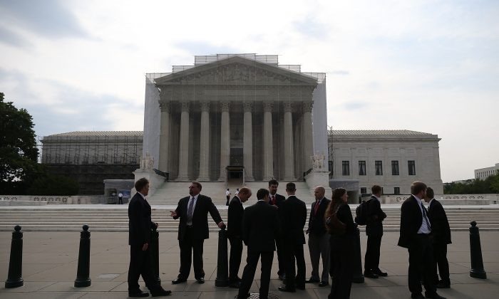 People stand in front of the U.S. Supreme Court building June 17, in Washington DC. On June 20 the high court ruled that prior state convictions should not be used to increase federal sentences for felons, and that arbitration contracts block plaintiffs from joining class action lawsuits. (Mark Wilson/Getty Images)