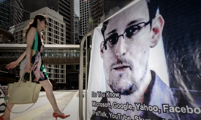 A woman walks past a banner displayed in support of former U.S. intelligence contractor Edward Snowden in Hong Kong on June 18, 2013. Snowden has recently begun revealing details of U.S. cyber operations against PRC-linked targets, a move that differs from the initial explanation he provided for why he was going public. (Philippe Lopez/AFP/Getty Images)