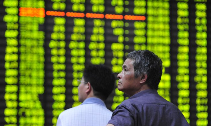 Investors watch the electronic board at a stock exchange hall on June 24, 2013 in Jiujiang, China, as stocks dropped sharply. The massive debt held in China's financial system may cause a sudden collapse of asset values. (ChinaFotoPress/Getty Images)