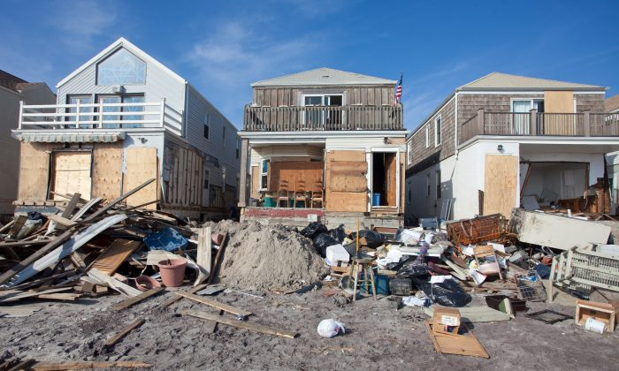 The beachfront home (C) of Bill Guage, a 64-year-old nurse, was slammed with water and sand during Superstorm Sandy. Yet the top floor remains undamaged and livable, and like other homeowners on the Rockaways, Guage plans to continue living in the house. (Amal Chen/The Epoch Times)