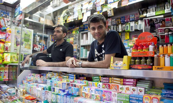 Clerks man Kishor Parekh's newsstand on 39th Street and Broadway, on June 5. Pictured in the photo are manager Kenny Patel (R) and Sam Patel. (Samira Bouaou/The Epoch Times)