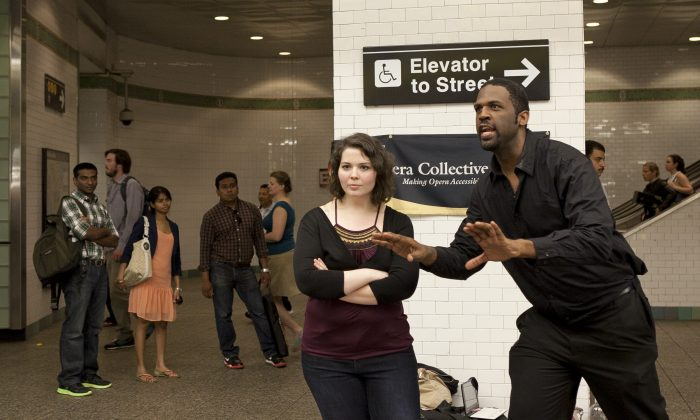 Opera Collective members Hannah Kramer and Quentin Lee sing opera inside the Times Square subway station on June 11. (Samira Bouaou/Epoch Times)