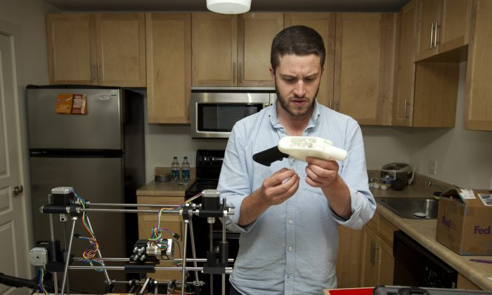 Cody Wilson works on the first completely 3D-printed handgun, The Liberator, at his home in Austin on Friday May 10, 2013. (Austin American Statesman, Jay Janner/AP Photo)