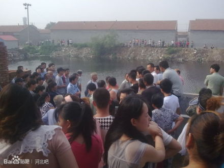 A crowd gathers in Yanshan County, Hebei Province after a migrant worker jumped into the river to avoid traffic policemen who were pursuing him. The policemen prevented the man from coming onshore, causing him to drown. (Weibo.com)