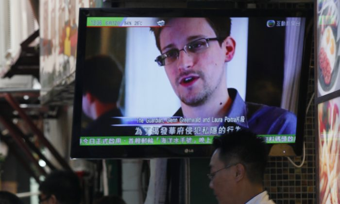 A TV screen shows the news of Edward Snowden, former CIA employee who leaked top-secret documents about sweeping U.S. surveillance programs, at a restaurant in Hong Kong on Wednesday, June 12, 2013. Snowden's disclosure of the NSA documents has been a propaganda windfall for the Chinese regime. (AP Photo/Kin Cheung)