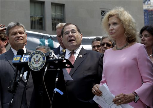 U.S. Rep. Jerrold Nadler,, center, flanked by Capt. Al Hagan, left, head of the Uniformed Fire Officers Association, and U.S. Rep. Carolyn Maloney, right, addresses a news conference near the World Trader Center site, in New York,  Monday, June 24, 2013. They are are joining community and labor officials and emergency workers top reach out to people who may have been physically affected by the 9/11 attacks to tell them they may still be eligible for health benefits. (AP Photo/Richard Drew)
