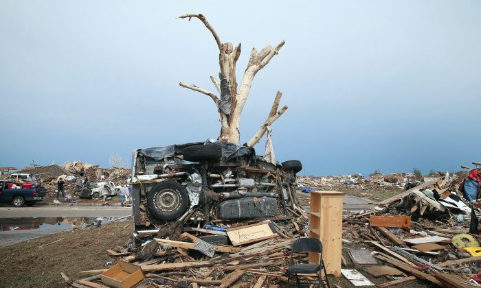 A pickup truck is wrapped around a tree after a powerful tornado ripped through Moore, Okla., on May 20, 2013. It is not safe to be in a car when a tornado hits, said research engineer Larry Tanner. (Scott Olson/Getty Images)