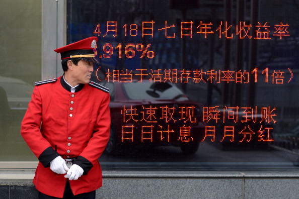 A guide stands in front of a bank in Beijing on April 23, 2013. (Wang Zhao/AFP/Getty Images)