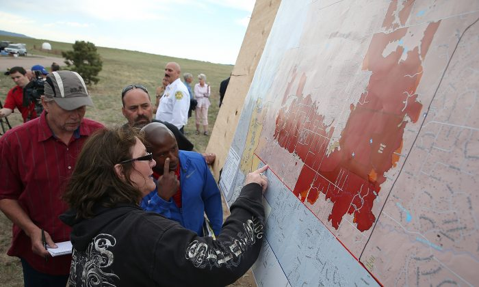 Residents look at a map showing the areas damaged by the Black Forest fire in Colorado Springs, Col., on June 14, 2013. John Bissett, president of the Housing and Building Association of Colorado Springs,  shares his story of personal hardship and professional feats as the fire nears containment on June 19, 2013. (Justin Sullivan/Getty Images)