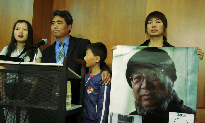Zhu Qiaofu with son speaks at a news conference to call for the release from prison of his brother Zhu Yufu. Their sister Zhu Xiaoyan holds up photo of Zhu Yufu, who is serving a seven year sentence for writing a poem. Person on the far left is a translator. News conference took place June 6. (Gary Feuerberg/ The Epoch Times)