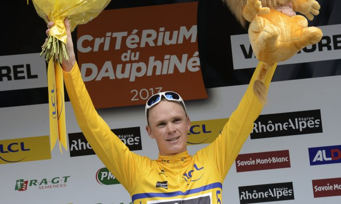 Sky's Christopher Froome celebrates his overall leader yellow jersey on the podium at the end of theStage Five of the Dauphine Criterium cycling race on June 6, 2013. Froome won the stage ahead of Spain's Alberto Contador and USA's Matthew Busche. (Jeff Pachoud/AFP/Getty Images)