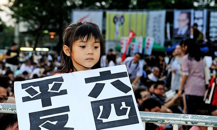"""A young participant in the commemoration of the Tiananmen Square massacre held on June 4, 2012, in Hong Kong holds up a poster saying """"Redress June 4."""" (Sung Pi Lung/The Epoch Times)"""