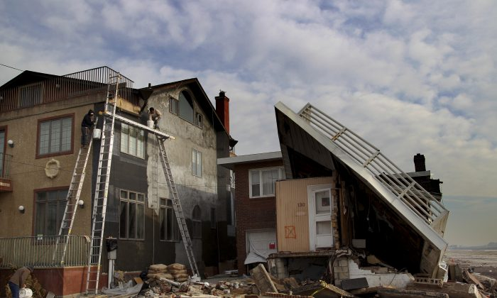 Men repair a home damaged by Superstorm Sandy next to a one that is almost collapsed on the Rockaway Peninsula in New York, Thursday, Nov. 29, 2012. Sandy damaged or destroyed 305,000 housing units in New York. (Seth Wenig/AP Photo)
