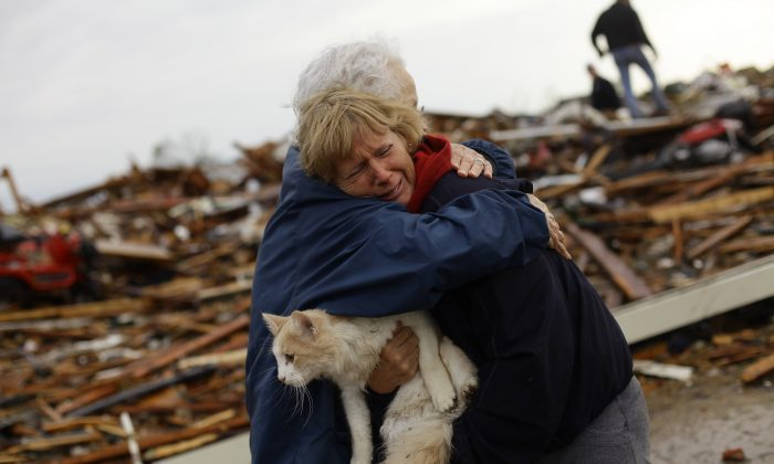June Simson (R) receives a hug from her neighbor Jo McGee while embracing her cat Sammi after she found him standing on the rubble of her destroyed home in Moore, Okla., on May 21, 2013. (Joshua Lott/AFP/Getty Images)