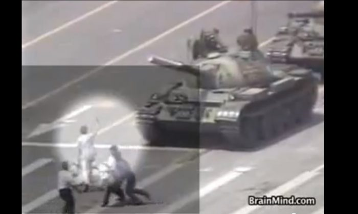 A screen grab from a video shot of the Tank Man shows two plain clothes police grabbing him and starting to hustle him off the boulevard.