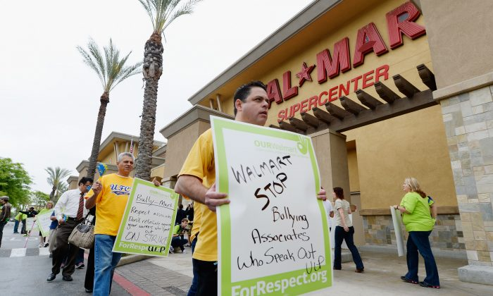 PICO RIVERA, CA - MAY 30: Walmart employees and their supporters walk a picket line to protest Walmart's retaliation against workers who speak out on May 30, 2013 in Pico Rivera, California. Some striking Walmart employees borded a bus to start a 1,500-mile bus journey titled 'Ride for Respect,'' ending at the company's annual meeting at its headquarters in Bentonville, Arkansas. (Kevork Djansezian/Getty Images)