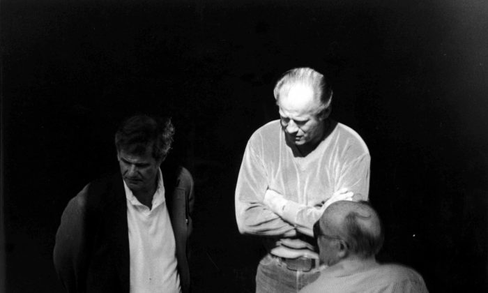 """This 1980 black and white surveillance photo released by the U.S. Attorney's Office and presented as evidence during the first day of a trial for James """"Whitey"""" Bulger in U.S. District Court in Boston, June 12, shows Bulger, center, with Ted Berenson, left, and Phil Wagenheim at a Lancaster Street garage in Boston's North End. Bulger is on trial for a long list of crimes, including extortion and playing a role in 19 killings. (AP/U.S. Attorney's Office)"""