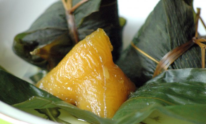 Eating the steamed rice, leaf-wrapped packages, zongzi, is an important custom during the Dragon Boat Festival. (The Epoch Times)