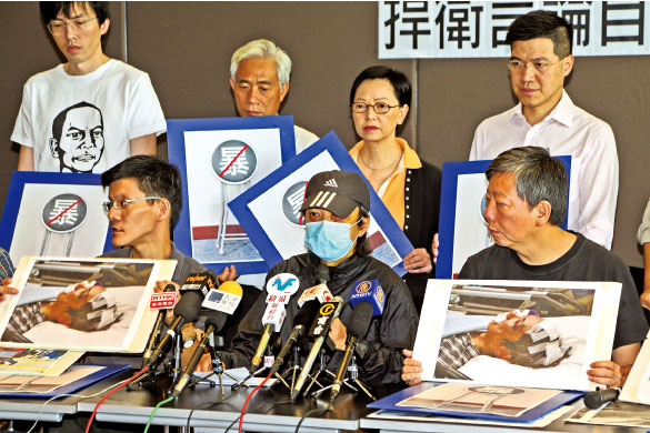 In the streets of Mong Kok, four assailants attacked Chen. Here Chen is pictured, accompanied by several people who attended the press conference on June 13. (Pan Zaishu/The Epoch Times)
