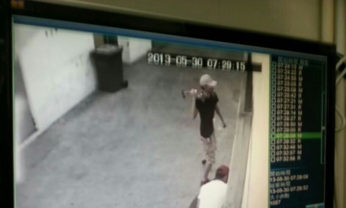 Unidentified men attack the door of the Epoch Times print shop in Hong Kong on the evening of May 30. The attack appeared to be part of a recent series of violent incidents directed against media organizations and individuals, which many in Hong Kong suspect may have been directed from mainland China. (Epoch Times)
