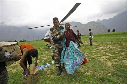 An Indian army soldier helps an injured Indian pilgrim after she was rescued from the higher reaches of mountains, at a makeshift helipad at Joshimath, India, June 24, 2013. Poor planning has hampered rescue operations in northern India, say experts, where more than 1,000 people are said to have died in landslides and flash floods.(AP Photo/Rafiq Maqbool)