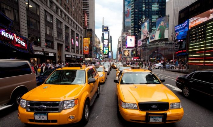 Yellow cabs drive through Times Square, file photo. New York is issuing 2,000 new yellow taxi medallions, which the city hopes will bring in upwards of $300 million in revenue. (Amal Chen/The Epoch Times)