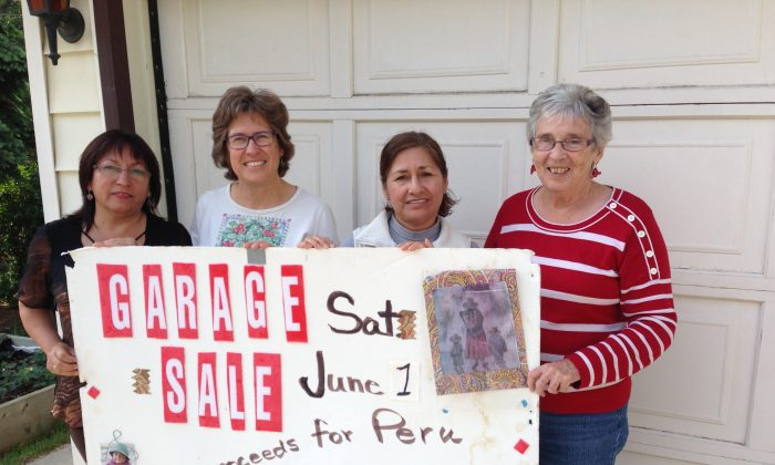 (L-R): Erla Hoyos, Maureen Sonntag, Vitalina Flores, and Pauline Maheux hold a sign in front of Sonntag's garage advertising a yard sale that raises money to help women in Peru. (Courtesy Maureen Sonntag)