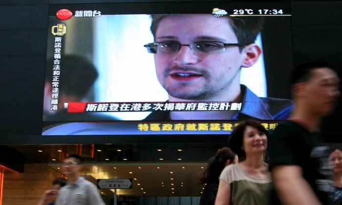 A TV screen shows a news report on Edward Snowden, a former CIA employee who leaked top-secret documents about U.S. surveillance programs, at a shopping mall in Hong Kong, June 23, 2013. Snowden was a hot potato in Hong Kong that the Chinese Communist Party has now palmed off, to the delight of Russia. (AP Photo/Vincent Yu)
