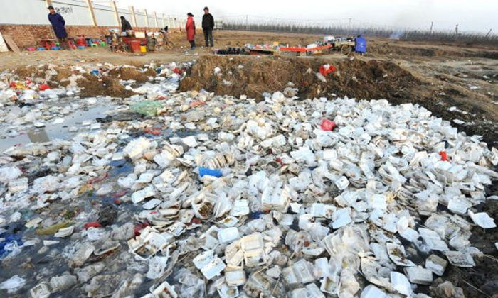 People stand near a landfill strewn with disposable lunch boxes outside a construction site in Hefei, capital city of Anhui Province. 40,000 counties and close to 600,000 villages in China are without any environmental protection infrastructure, while creating 280 million tons of waste annually. (Getty Images)