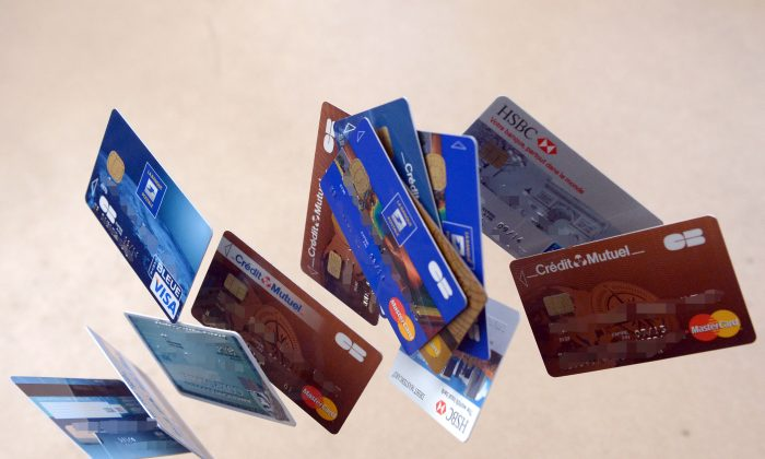 Payment cards falling down are pictured in this photo montage. In the United States, pre-paid debit cards are becoming ever more popular, but they carry certain drawbacks. (Damien Meyer/AFP/Getty Images)