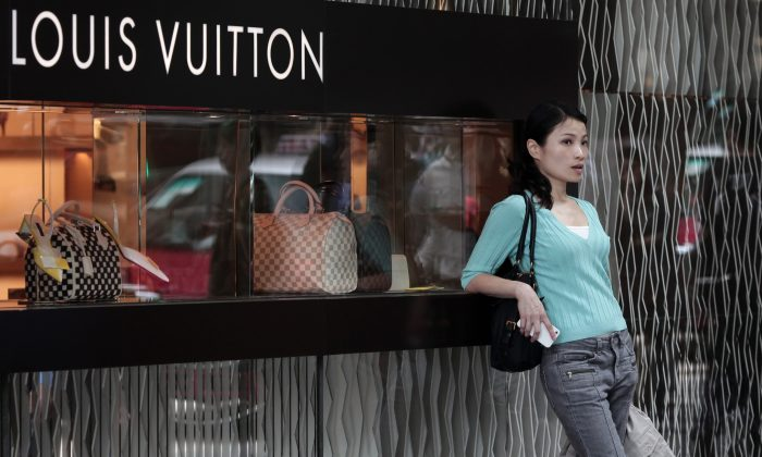 In this file photo, a Chinese woman leans on a Louis Vuitton shop display window in Hong Kong, on April 23, 2013. While cashed-up Chinese who travel to the Hong Kong for luxury shopping, the poorest 5 percent of Chinese households live on US$163 per year. (Anthony Wallace/AFP/Getty Images)