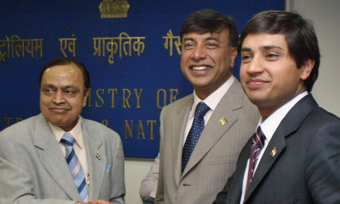 In this Wednesday, July 25, 2007 file photo, ArcelorMittal Chief Executive Officer Lakshmi Mittal, center, watches as his son Aditya Mittal, right, shakes hands with Indian Petroleum Minister Murli Deora, left, at a press conference in New Delhi, India, where he said ArcelorMittal was committed to setting up 10 million tonne capacity steels plants each in Jharkhand and Orissa states. ArcelorMittal, the world's largest steelmaker, has abandoned plans for an $8.5 billion steel plant in the eastern Indian state of Orissa in the second major blow this week to the government's efforts to lure foreign investment. The company said Wednesday, July 17, 2013, it decided to scrap the steel plant in Orissa state after a seven year delay in acquiring land. (AP Photo/Mustafa Quraishi)